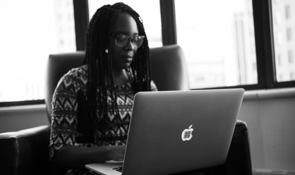 Monochrome photo of a woman of color working on a laptop